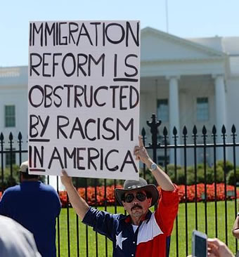 Texan holds immigration reforn sign denouncing racism at White House